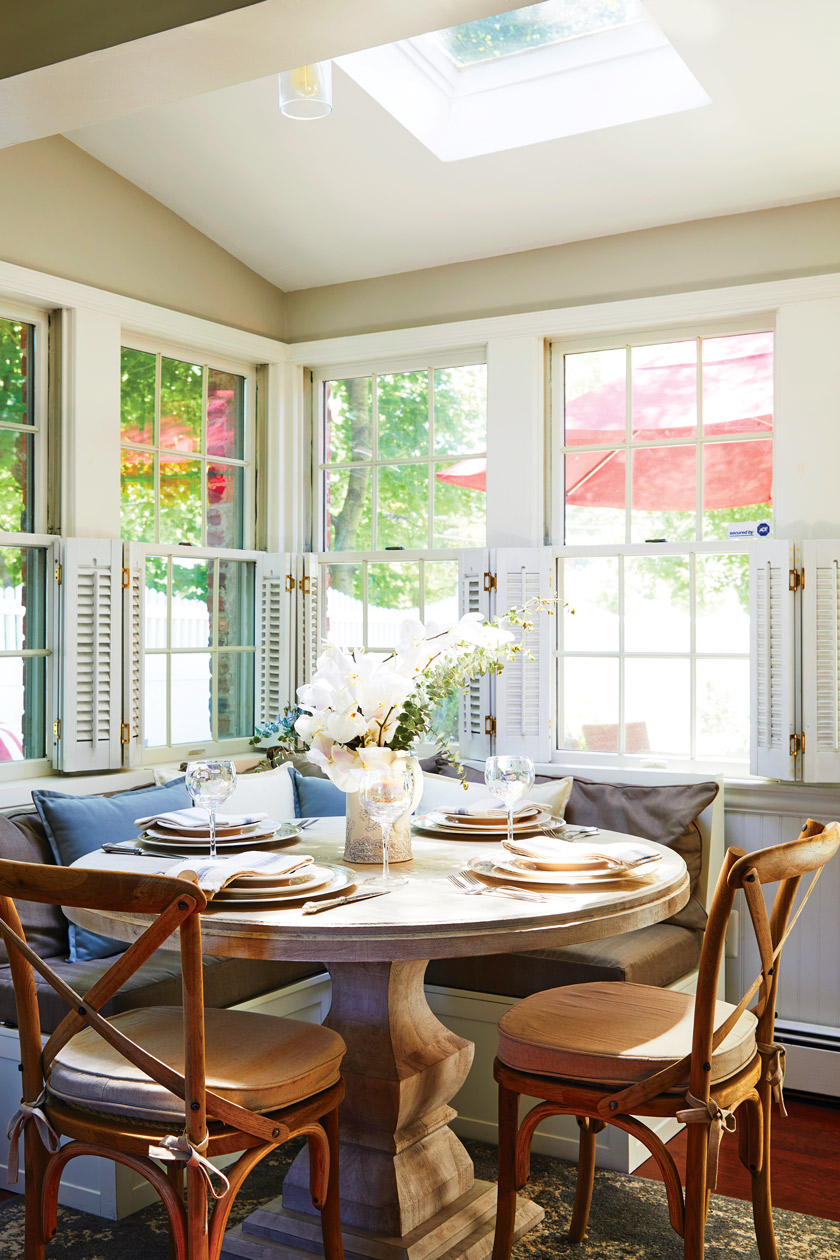 sunny view of dining nook with round table, two chairs and bench seating