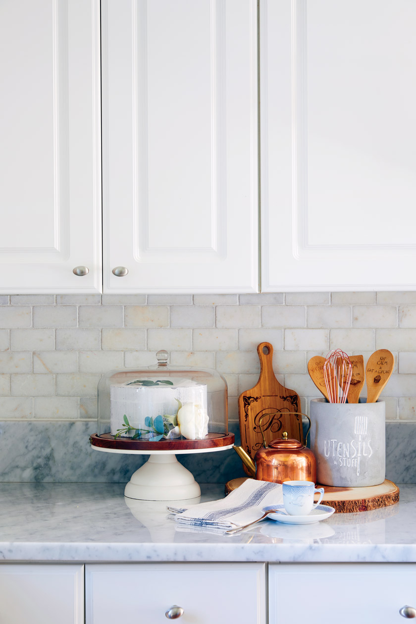 white kitchen counter iwth vignette of wooden and copper tools and accessories
