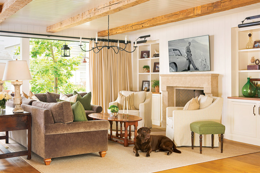 A dreamy living space, the custom limestone fireplace, vintage wood beams and individually planked shiplap capture the true essence of a European farmhouse.