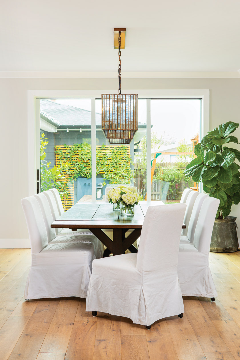 dining area with large coastal patio doors, a long dark wooden table and 8 chairs with white chair covers