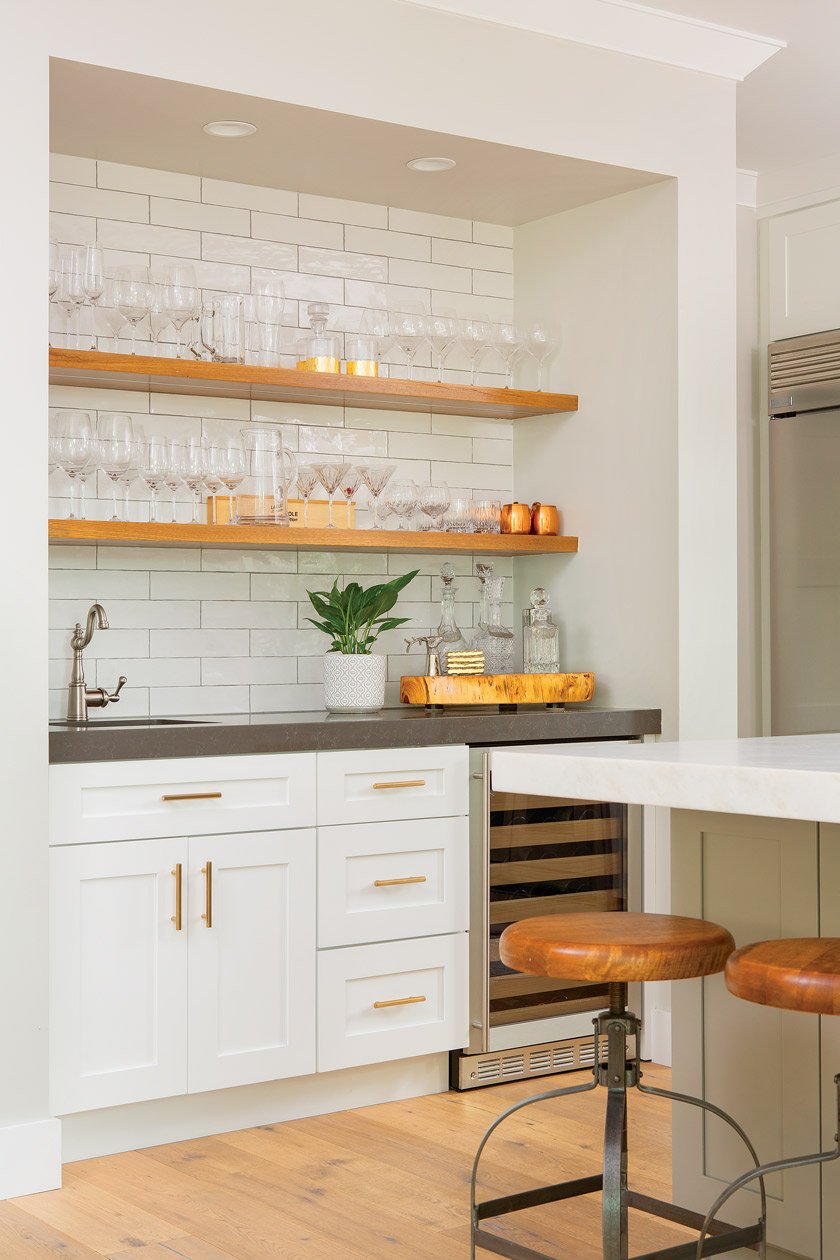 white kitchen with white subway tile, open natural wood shelving adorned with glassware, brass hardware and gray countertops