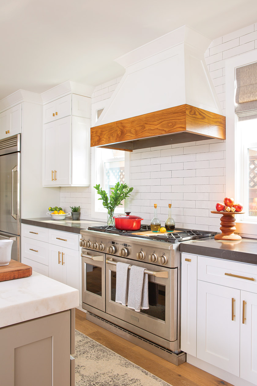 white kitchen with stainless steel double wide stove with white and natural farmhouse wood hood above stove