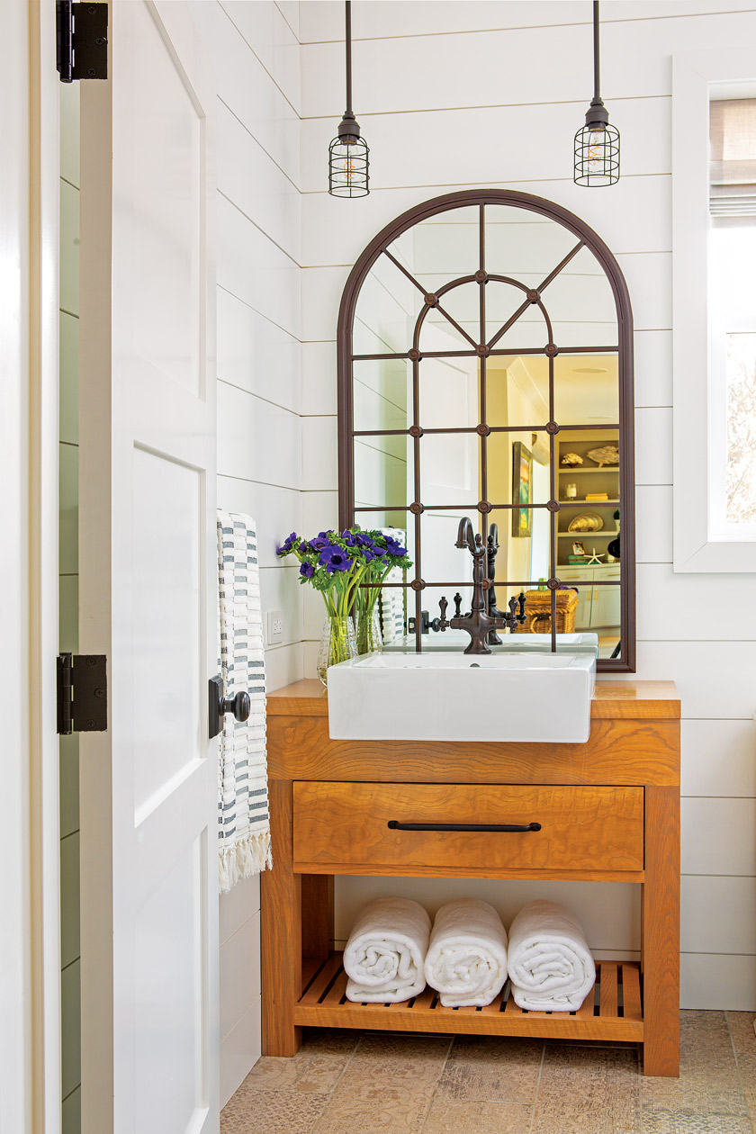 guest bathroom with natural wood vanity, white square sink, arched mirror above and two pendant lights above