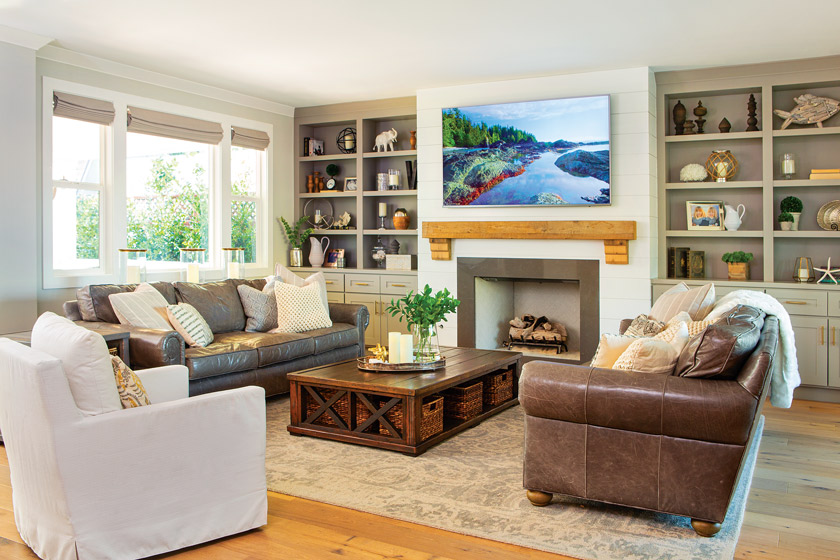 living room with open shelving, large television, white chair, leather sofa and fireplace