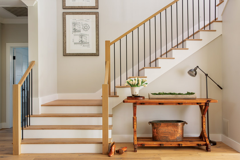 white and natural wood coastal farmhouse style open stairway with neutral wall art and small table with accessory at base of stairs