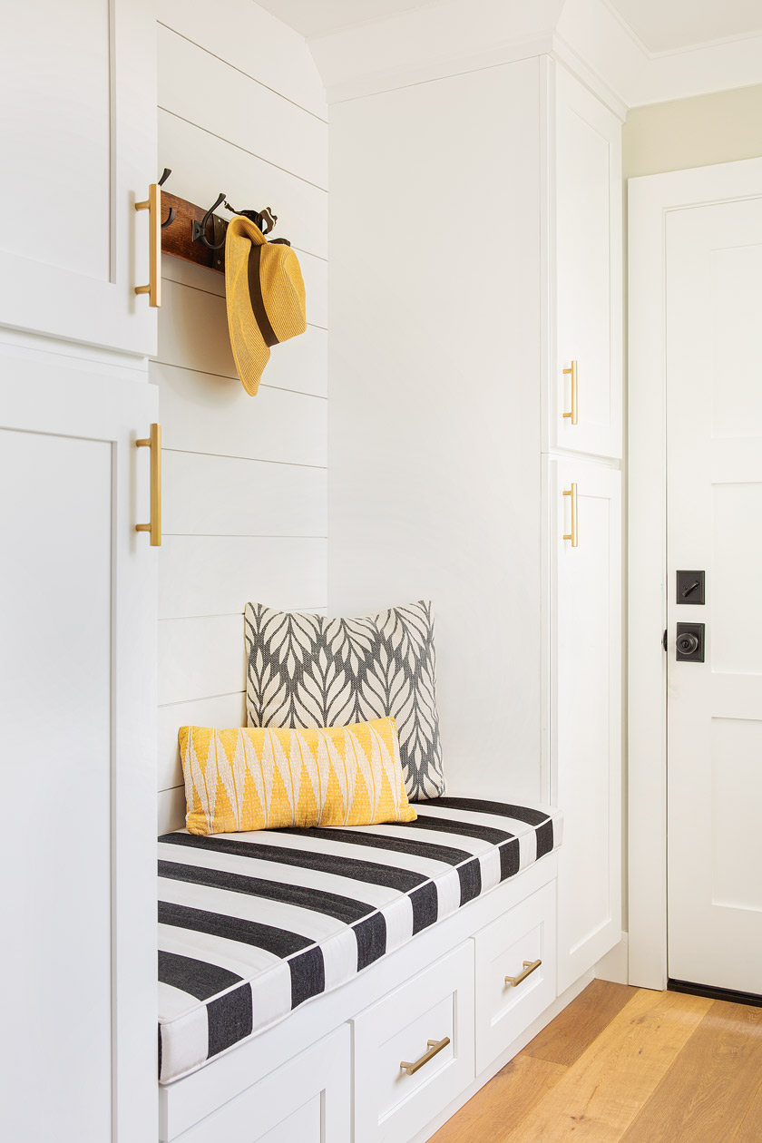 white mudroom/storage area with black and white striped bench cover and yellow pillow and straw hat hanging above