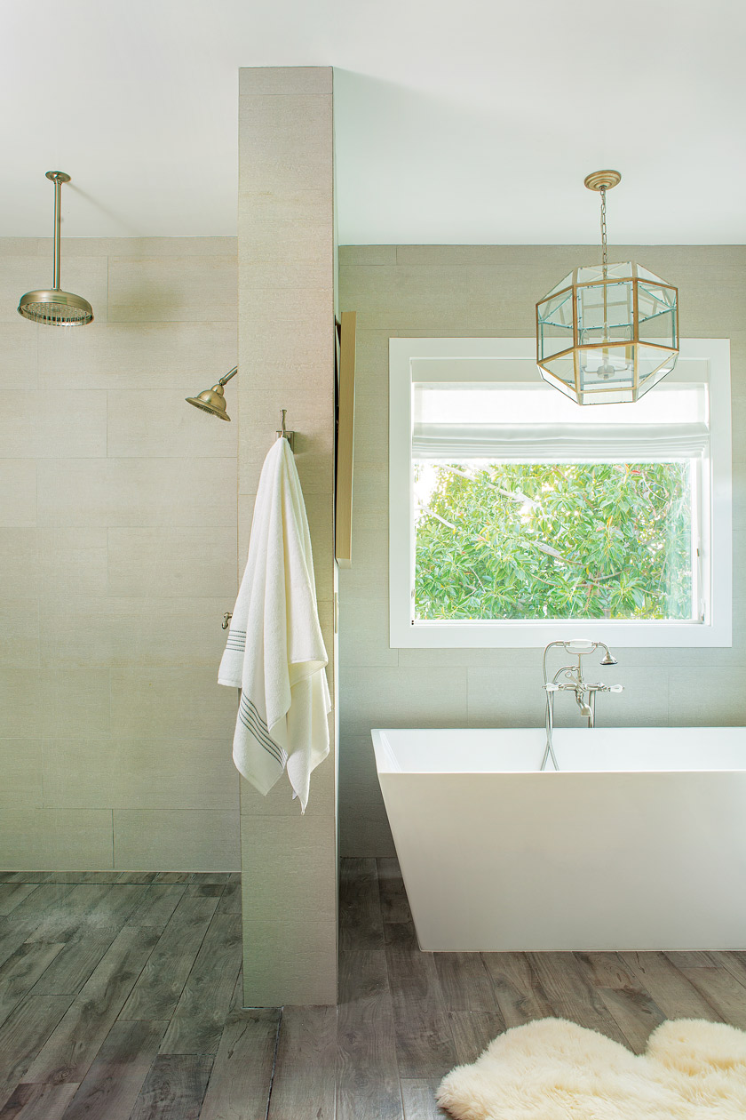 white bathroom with white tub, open shower, window with green tree in view