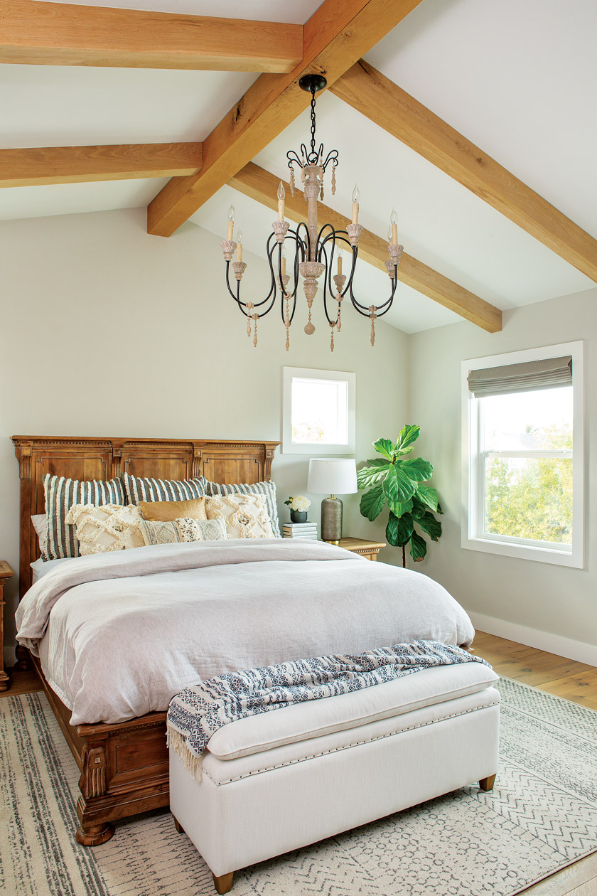 white master bedroom with large chandelier and natural farmhouse wood open beams