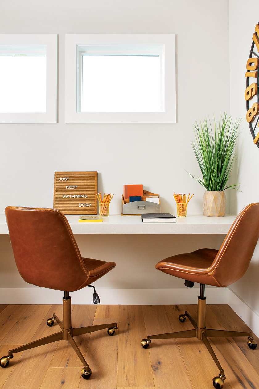 desk area in a coastal farmhouse with two brown leather swivel chairs beneath two smaller windows