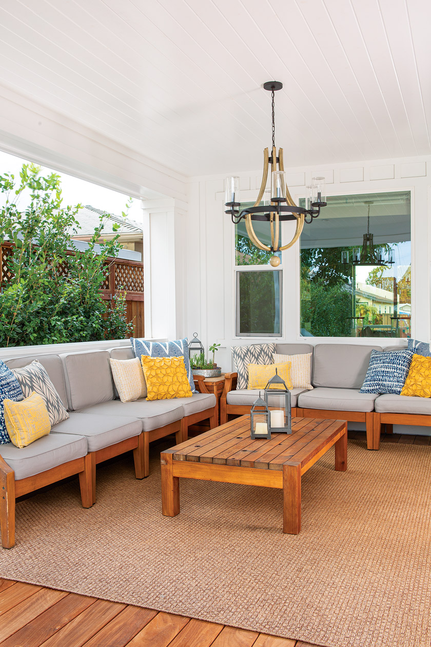 open patio with large sectional seating with yellow and coastal blue pillows and teak table with large chandelier above