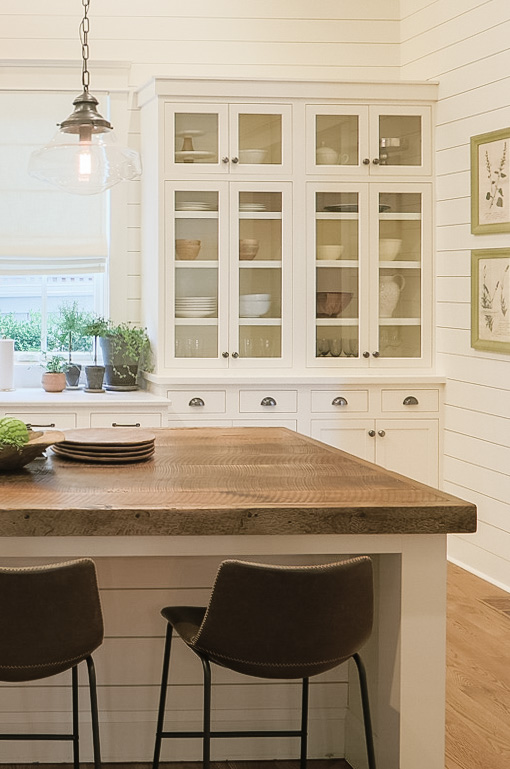 Creamy white walls and cabinets bring a vintage vibe to this interior.