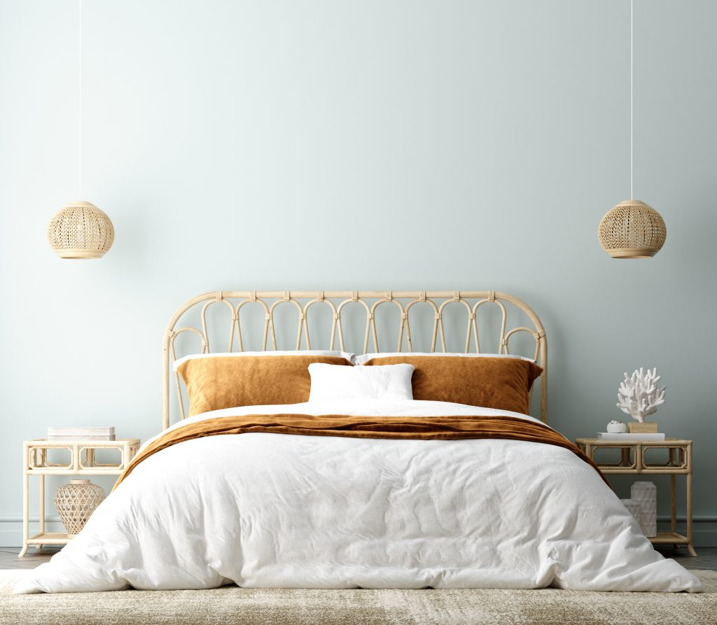 This boho coastal bedroom mixes neutral textures that complement both styles. The blue wall and sculpture read coastal, while the lighting and headboard have a boho feel. [Photo courtesy of iStock/Artjafara]